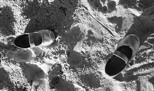 A pair of childrens shoes in the sand. Foto