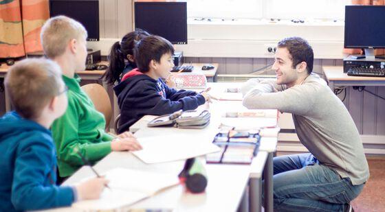 Elever som sitter ved pulter i rekke, lærer som snakker med dem. Fotot