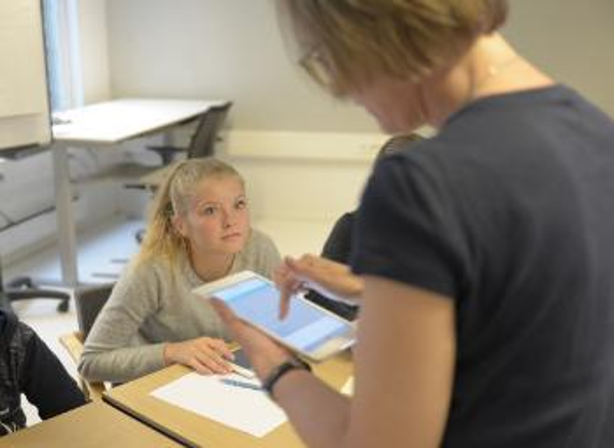 Jente på ungdomstrinnet bak pulten, lærer med nettbrett foran. Fotot