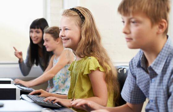Elever foran PC-er i et klasserom. Foto
