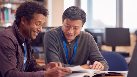 To mannlige lærere ser i en bok sammen og smiler. Foto.