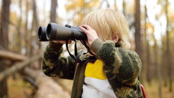Boy on a forrest trail looking into binoculars.