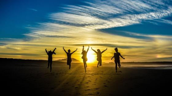 Photo illustration showing silhouettes of young people jumping un the beach at sunrise.
