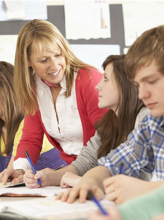 Kvinnelig lærer snakker med ungdommer i klasserom. Foto.