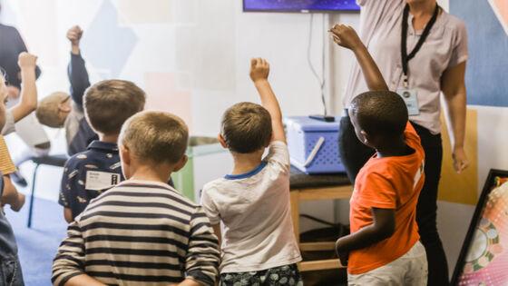 Elever som rekker opp hånden i klasserommet