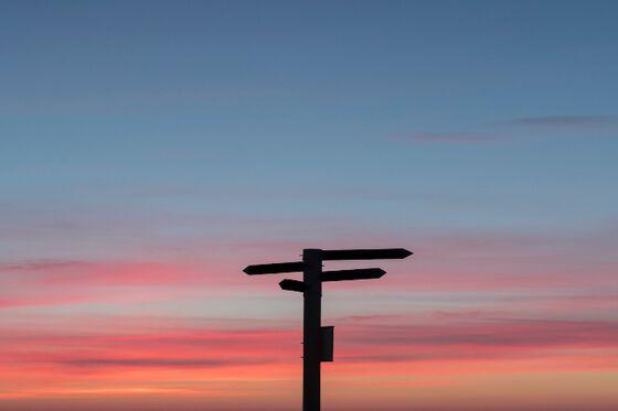 Skilt som peker i ulike retninger med solnedgang i bakgrunnen