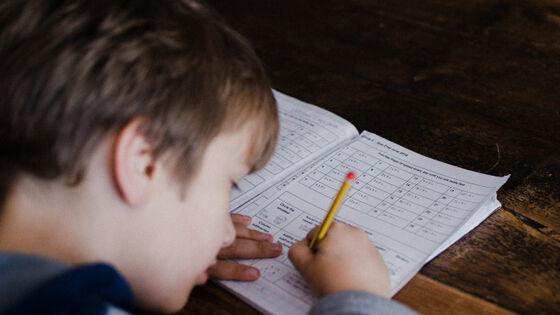 Gutt skriver i hefte. Foto.