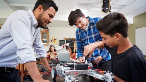 Elever og lærer utfører og en fjernstyrt robot i klasserommet. Foto.