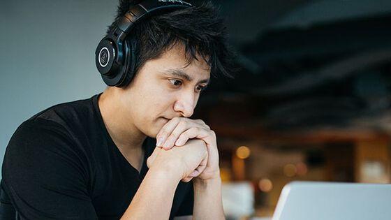 Mann foran pc-skjerm med hodetelfoner