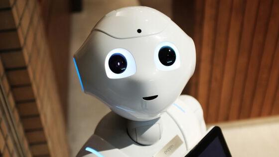 Roboten Pepper ser i kamera med nettbrett i hendene