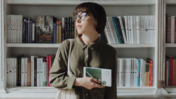 Jente med bok foran bokhylle