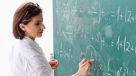Lærer skriver på tavla. Illustrasjonsfoto.