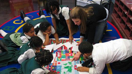 Elever som leker på gulvet med lærer