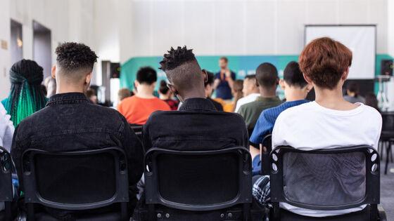 Skolelever sitter med ryggen til i klasserommet