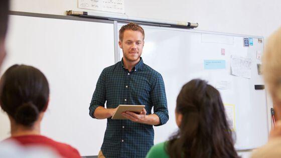 ung mann står foran whiteboard-tavle i klasserom og snakker.