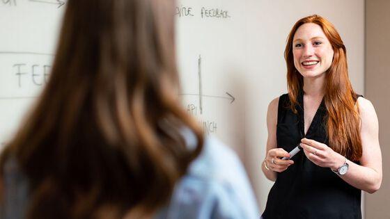 Illustrasjonsfoto av to kvinner i samtale foran tavle (Illustrajonsfoto fra: ThisisEngineering RAEng på Unsplash).