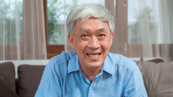 Eldre kinesisk mann som smiler. Foto.