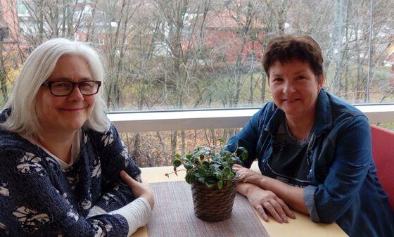 To damer rundt et bord foran et stort vindu