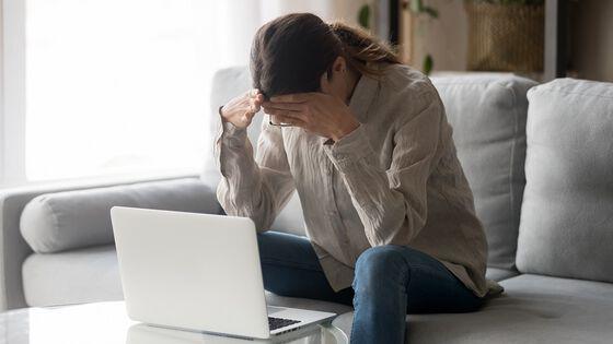 fortvilet dame foran laptop som sitter på sofaen.foto.