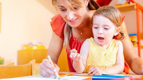 Bilde av barnehagelærer og et barn som sitter sammen. Barnehagelæreren tegner med en grønn blyant mens barnet ser på og virker engasjert.
