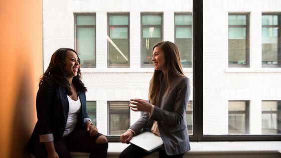 to unge kvinner som sitter glade i vundueskarm og diskuterer. Illustrrasjonsfoto
