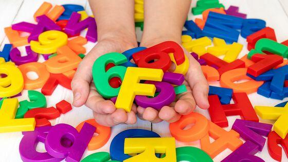 barnehender som holder bokstaver og tall