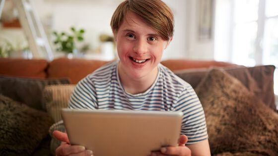gutt med downs syndrom som sitter i sofaen blid og fornøyd med sin laptop