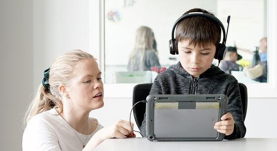 bilde av lærer som hjelper elev på nettbrett