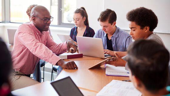 En lærer snakker med elever som bruker nettbrett og bærbar PC i klasserommeti