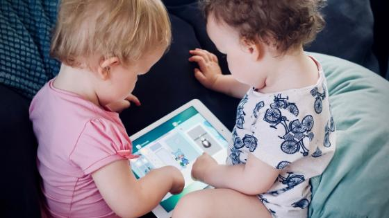 Bilde av to småbarn som sitter på sofa og bruker nettbrett