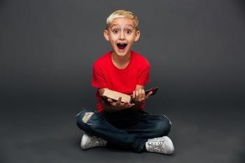 Smiling boy with a red t-shirt holding a book