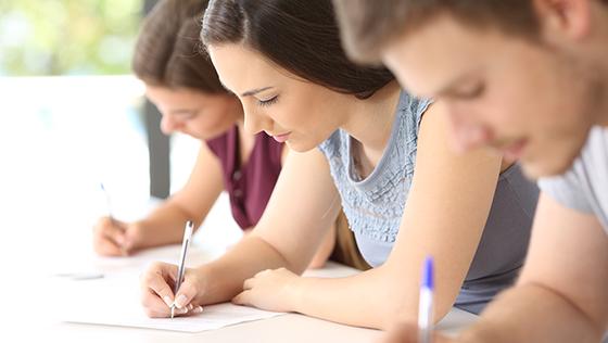 Tre studenter skriver på ark