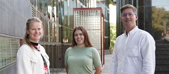 Tre mennesker foran en bygning på UiO