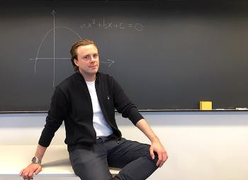 Alexander Jonas Viktor Selling sitting in the classroom in front of a blackboard with a graph drawn on it