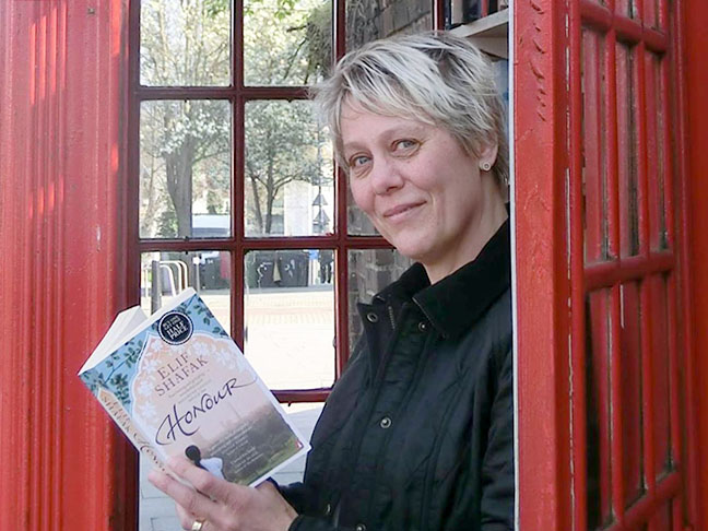 Anna Nissen standing in a phone box library reading a book