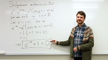 Jóhann Örn Sigurjónsson in front of a white board with a mathematics formula