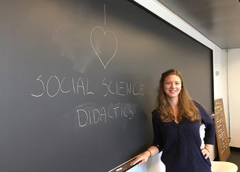 Nora Elise Hesby Mathé standing in front of black board where she has written: I love social science didactics